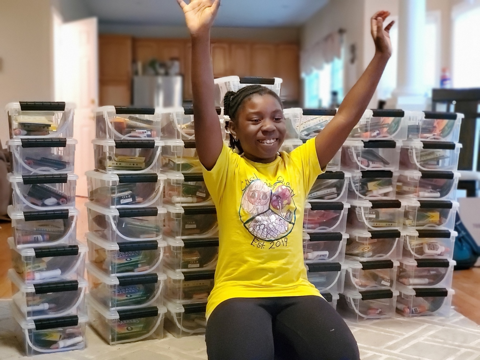 Chelsea Phaire with her hands up in excitement in front of art kits